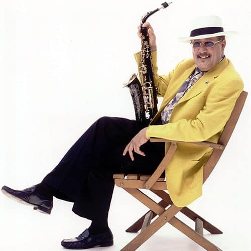 Paquito in Yellow Jacket Sitting Holding Sax