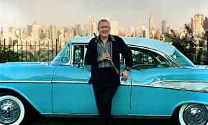 Paquito Standing Next to Blue Car Manhattan skyline