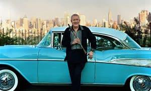 Paquito Standing Next to Blue Car Manhattan skyline