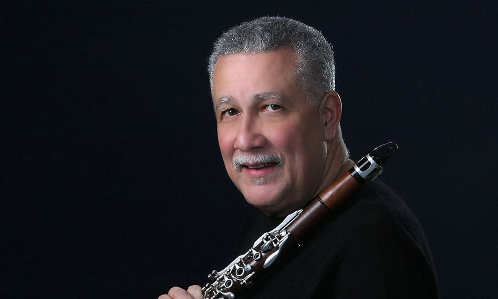 Paquito D'Rivera holding clarinet with black background